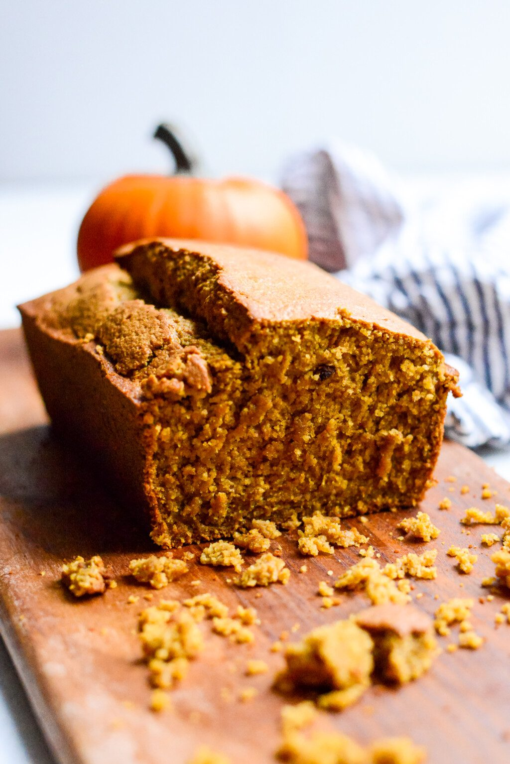 close up of a cut loaf of gluten free pumpkin bread on wooden cutting board