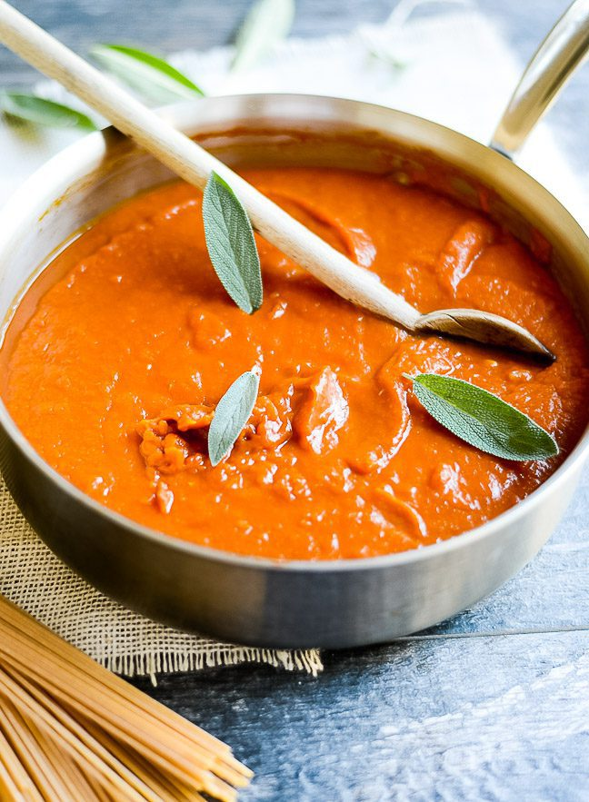 a sauce pan filled with pumpkin pasta sauce being stirred by a wooden spoon