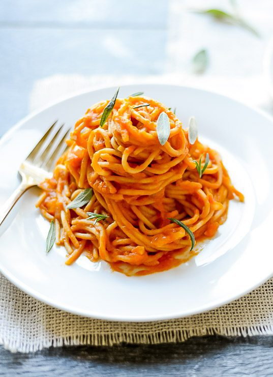 spaghetti on a white plate covered in pumpkin pasta sauce with fresh sage and rosemary on top