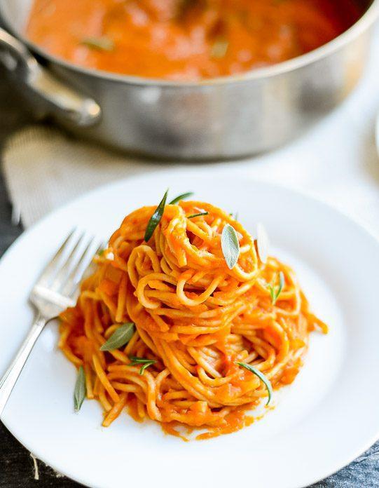 closeup of spaghetti with an orange pasta sauce on a white plate