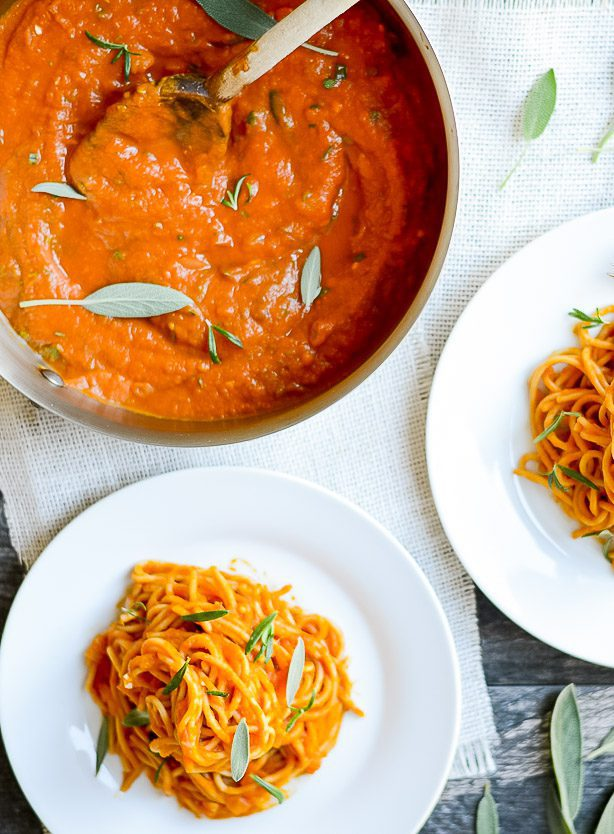 top down view of plated spaghetti with pumpkin pasta sauce alongside a saucepan with fresh herbs