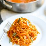 Spaghetti pasta covered in an orange pumpkin pasta sauce.