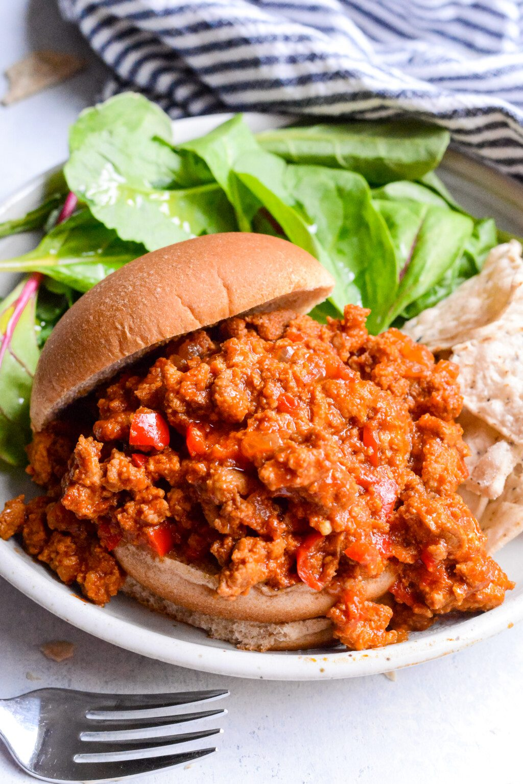 close up of slow cooker turkey sloppy joes on a white plate with leafy greens