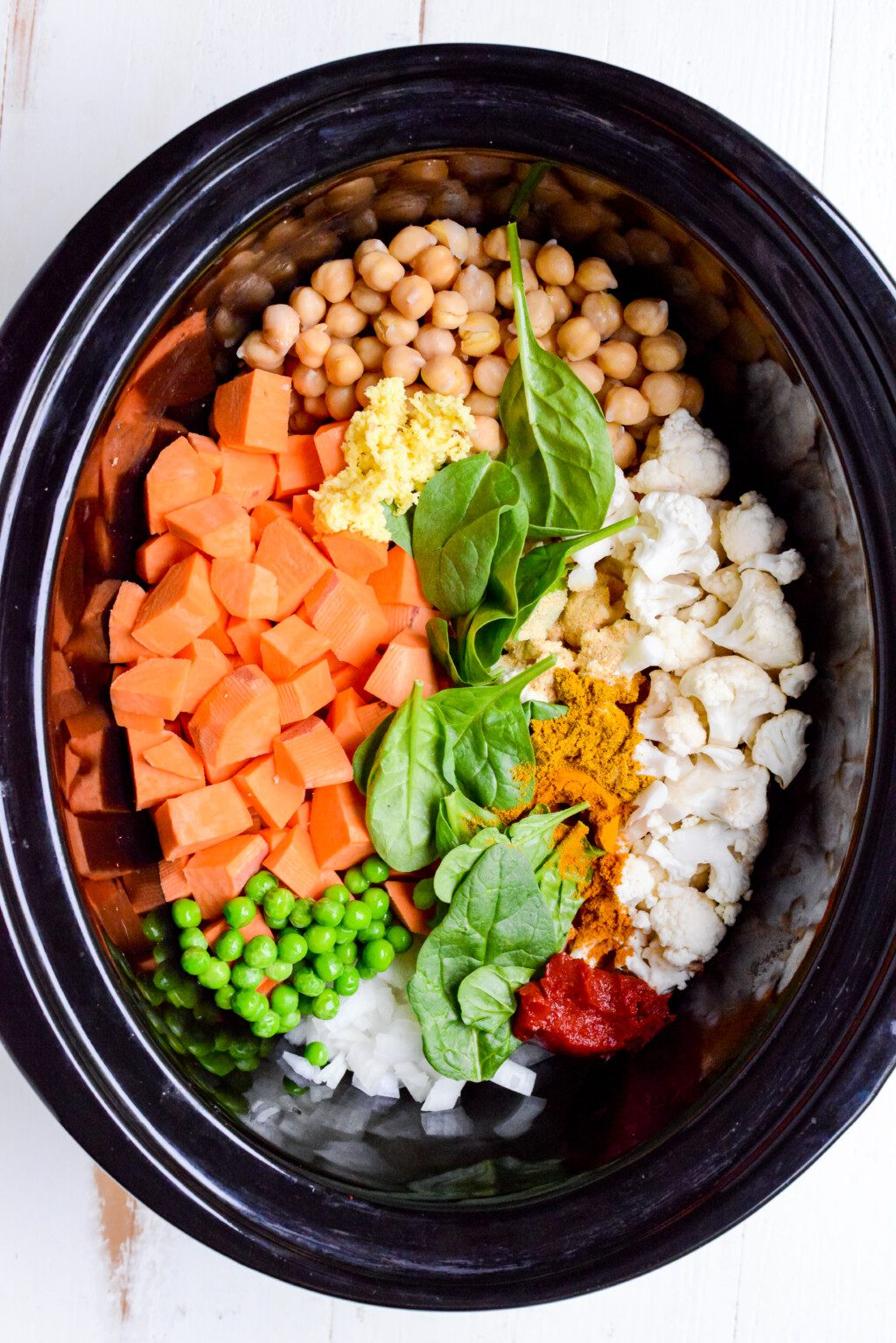 top down view of ingredients for slow cooker vegetable curry in black crockpot