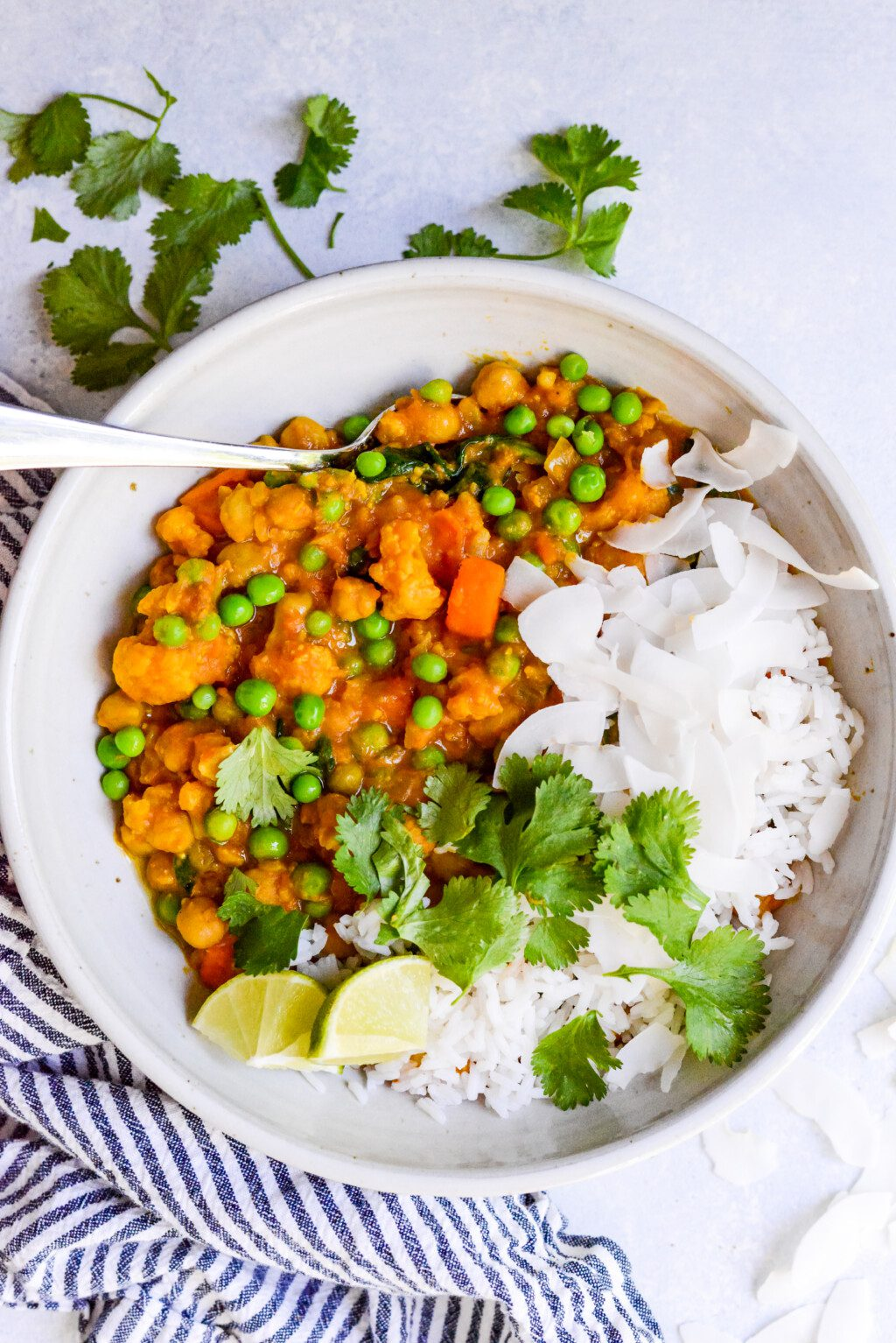 close up of a white bowl of vegetarian curry with lime wedges and white rice